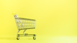 Shopping cart on yellow background. Minimalism style. Creative design. Copy space. Shop trolley at
